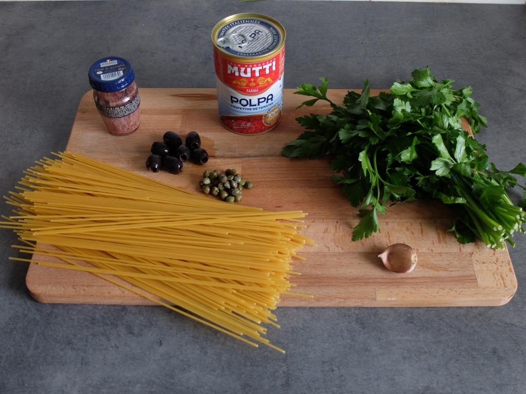 Les ingrédients nécessaires à la recette : pâtes, ail, olives noires, câpres, anchois, persil et huile d'olive.