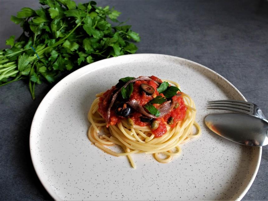 Un plat de spaghetti avec une sauce tomate aux anchois, aux câpres, aux olives et à l'ail