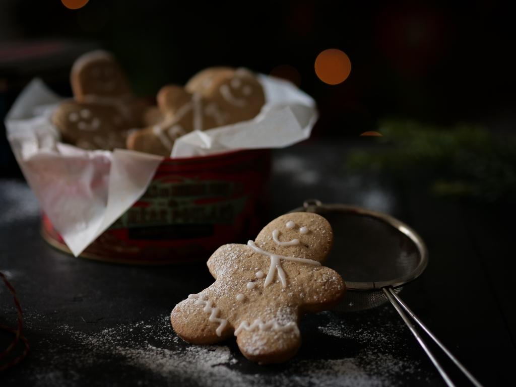 Un gingerbread au premier plan et un arbre de Noël au second plan et du sucre glace pour imiter la neige sur fond noir.