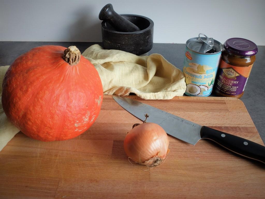 Les ingrédients nécessaires au curry de potiron : une boite de lait de coco, une boite de pâte de curry, un oignon, un potiron et un bon couteau.