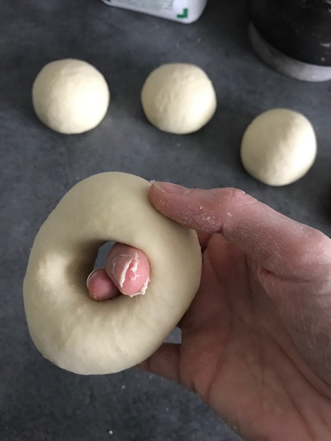 Prenez une boule de pâte à bagel, faites un trou avec votre index et agrandissez le trou à deux mains.