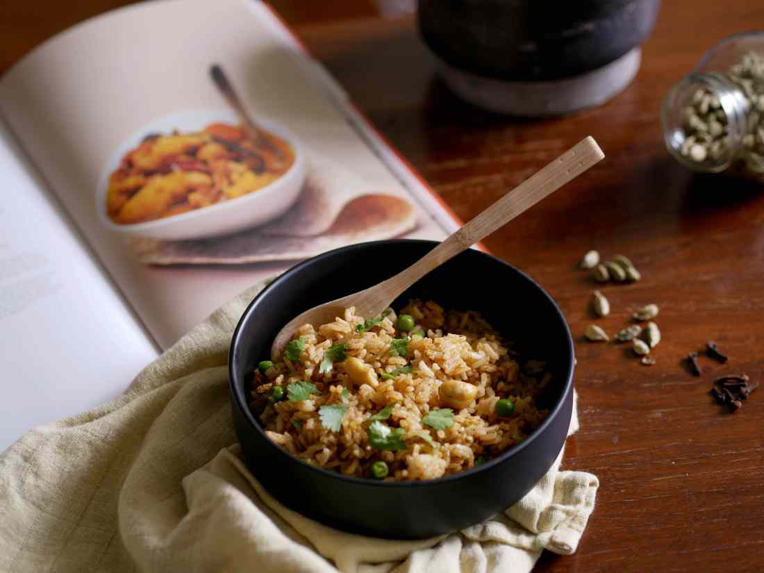 Plat de byriani présenté avec les épices autour et un livre de cuisine