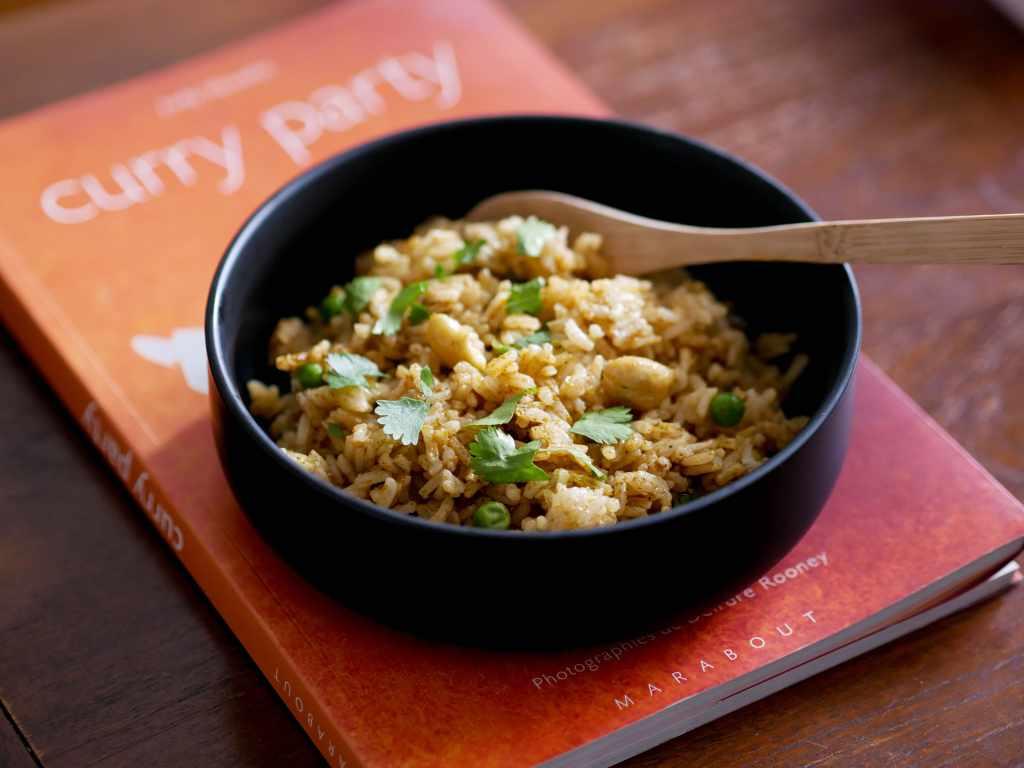 Assiette de byriani posée sur un livre de recettes indiennes