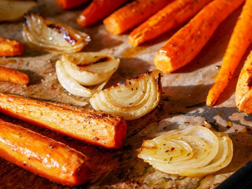 Gros plan sur des carottes et des oignons rôtis