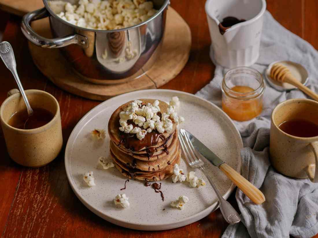 Crumpets avec du chocolat, du pop-corn sur une jolie table dressée avec du thé et des atsses