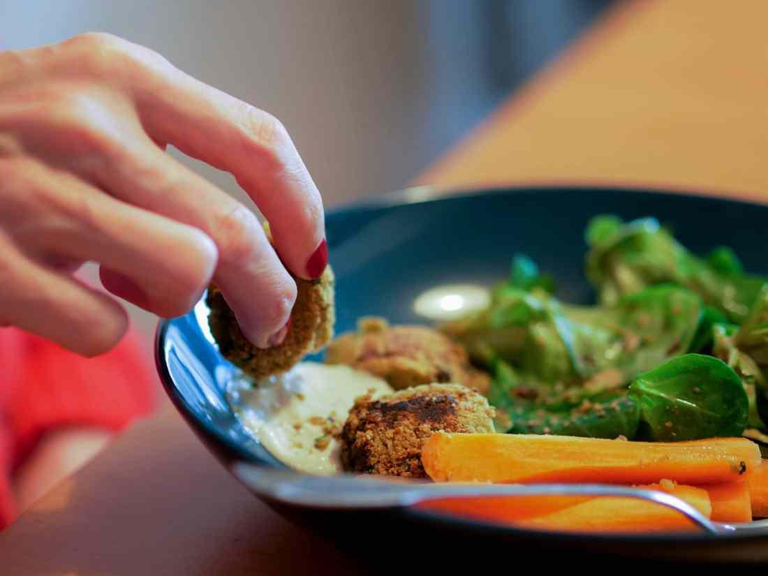 Une main trempe un falafel dans une sauce au sésame appelée tahini