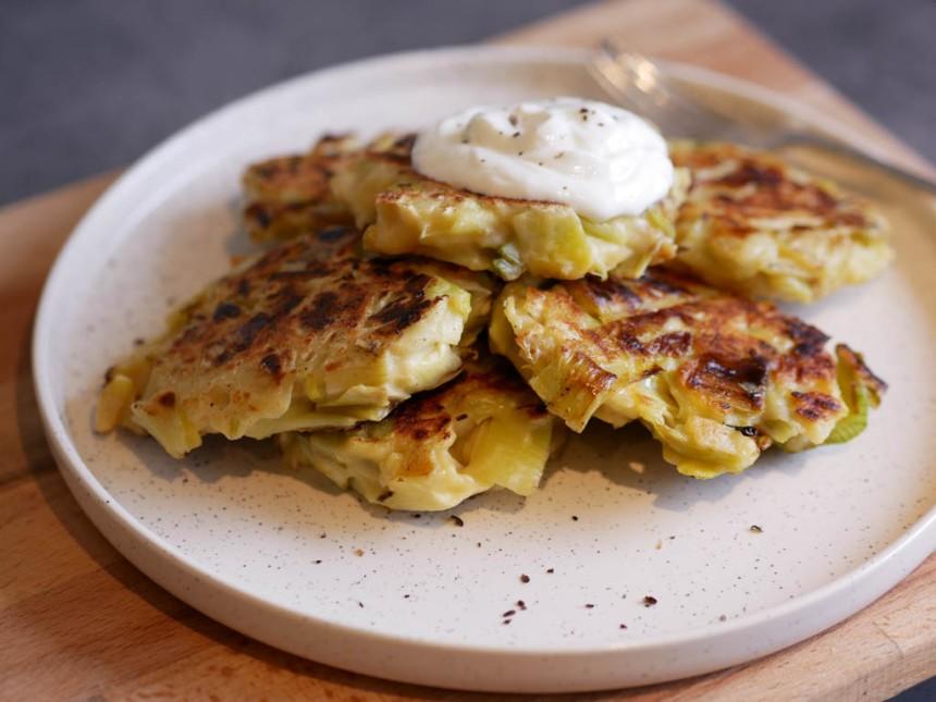 Pancakes aux poireaux superposés avec de la crème fraîche sur le dessus.
