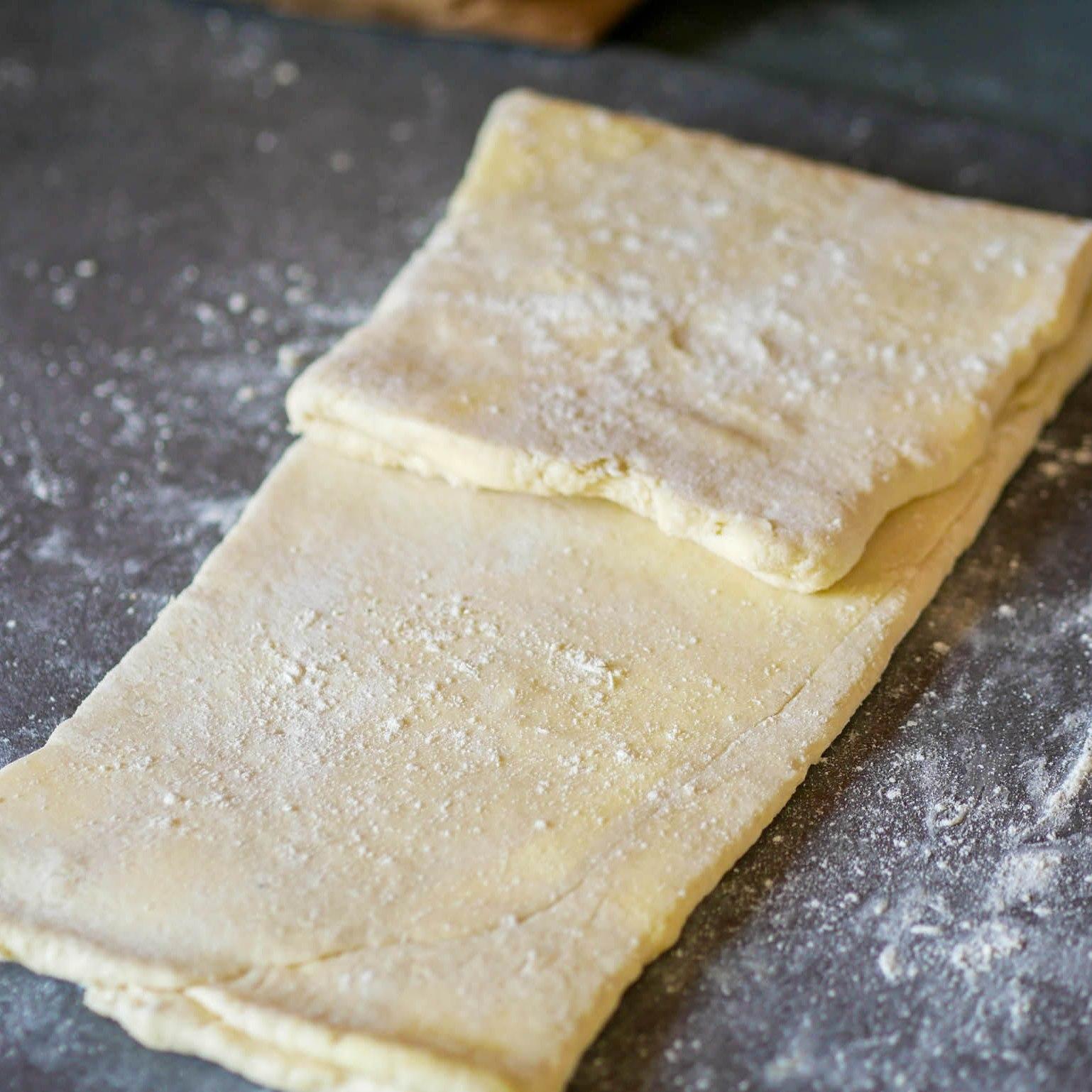On replie le bord supérieur, puis l'inférieur, puis on réétale la pâte, on la tourne d'un quart de tour avec les plis sur le côté
