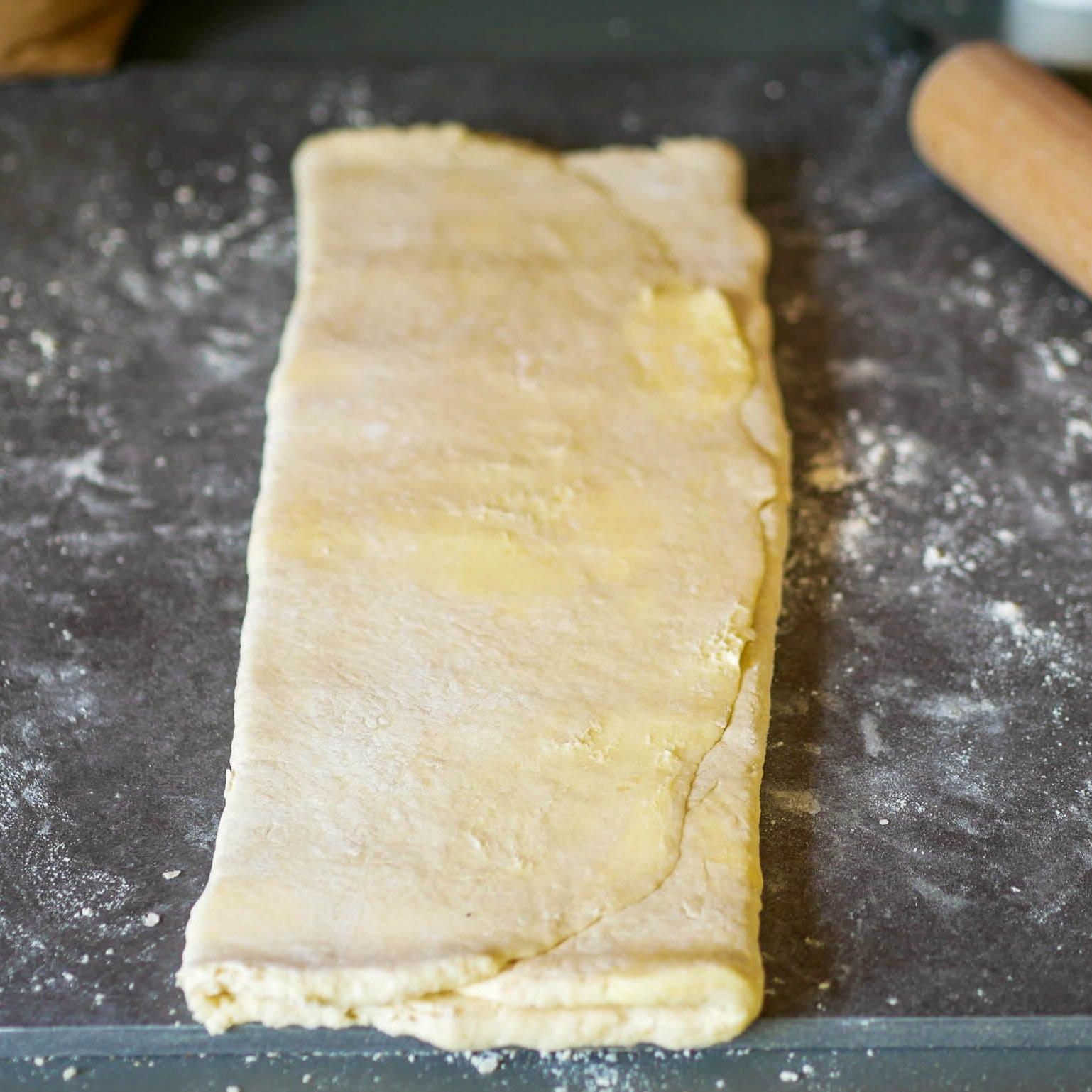 On tourne la pâte d'un quart de tour avec les plis sur le côté droit et on recommence les plis