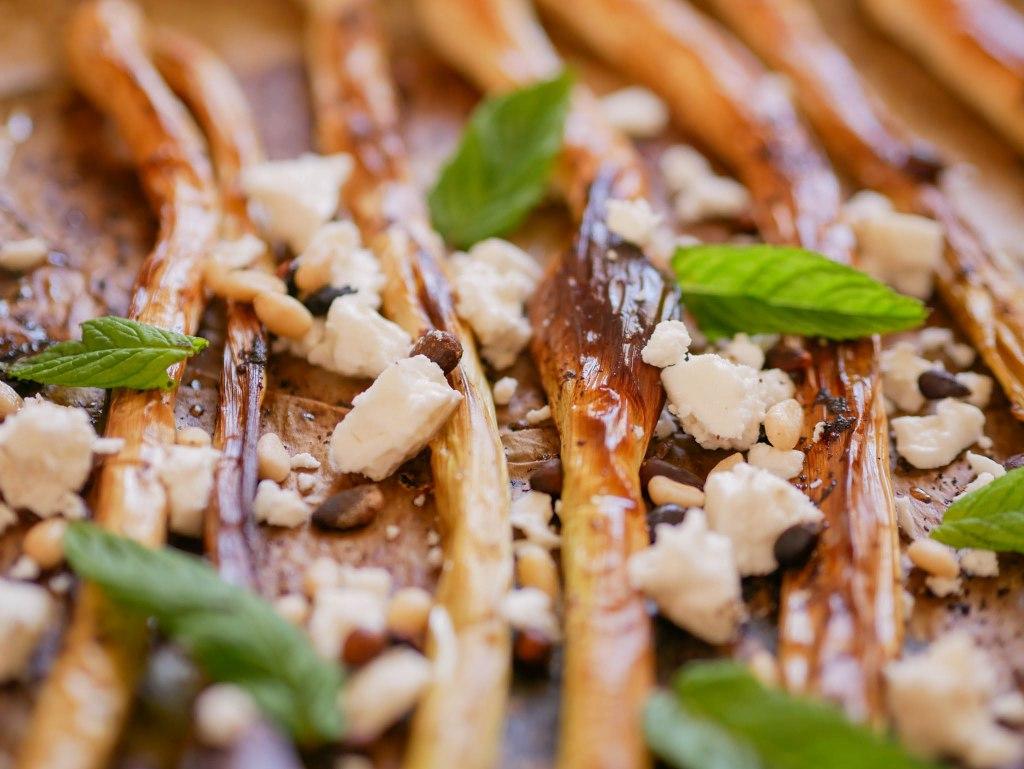 Gros plan sur les poireaux rôtis sortis du four avec la feta, la menthe et les pignons....