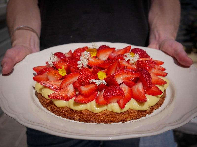 Deux mains tiennent la tarte aux fraises