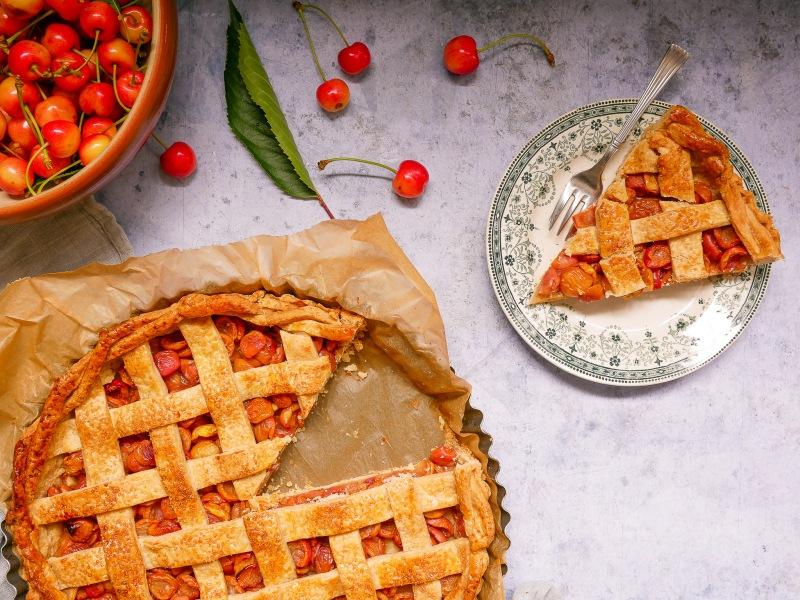 Part de tarte découpée avec la cherry pie sur le côté et un saladier de cerises