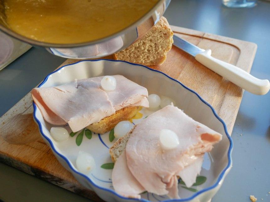 Versez le fromage fondu sur le pain, le jambon et les oignons grelots