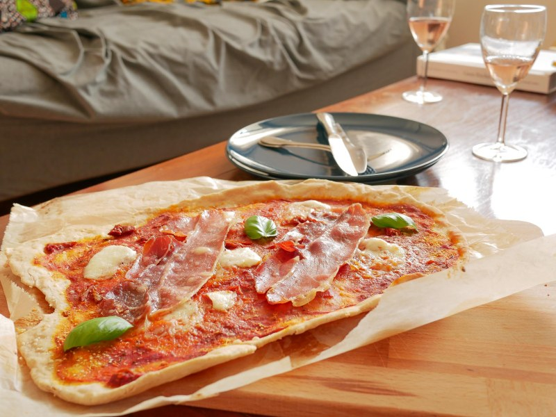 Pizza posée sur une table avec des verres de vin