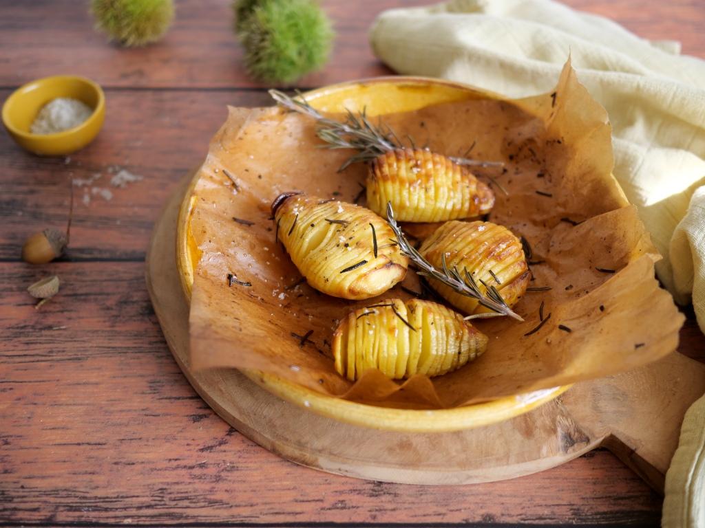 Pommes de terre posées dans un plat avec des chataignes autour, du gros sel.