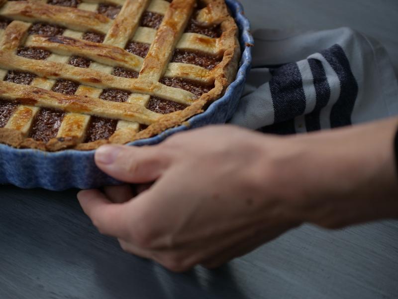 Une main qui dépose la tarte sur une table