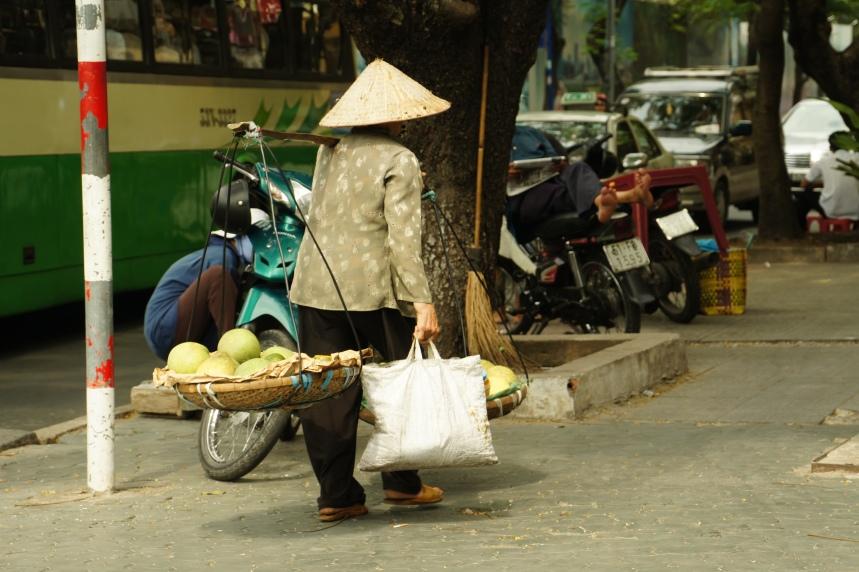 Une femme portant un chapeau pointu au Vietnam et de lourdes charges sur les épaules