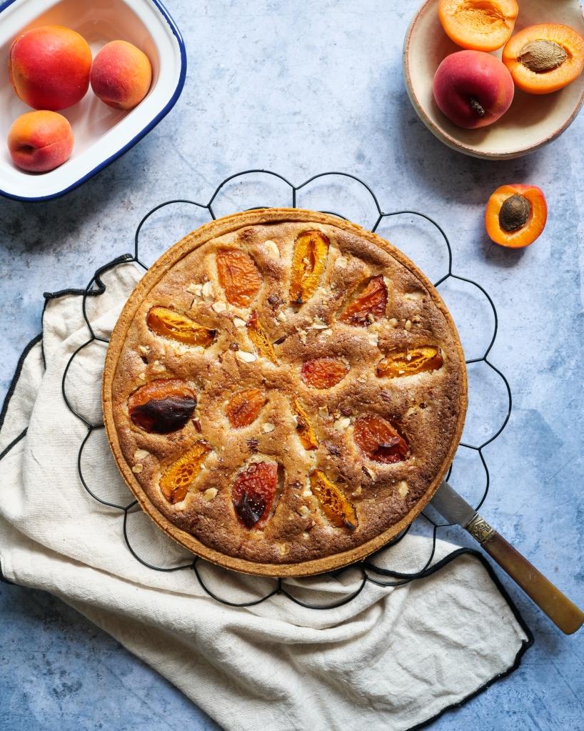 Tarte à l'abricot déposée sur une table avec des abricots autour et un torchon sur le côté. Jolie couleur ensoleillée.