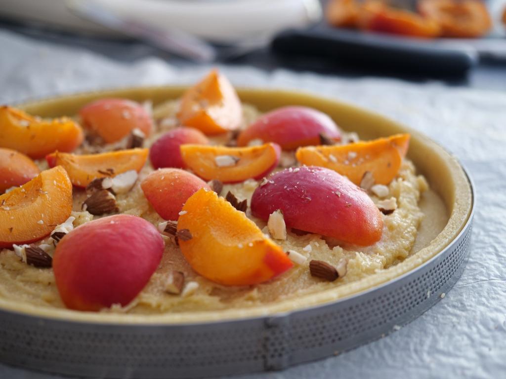 Pâte à tarte, crème d'amande et abricots prêt à être enfournés.